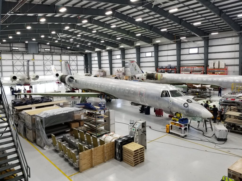 aircraft being worked on in maintenance hanger with no paint