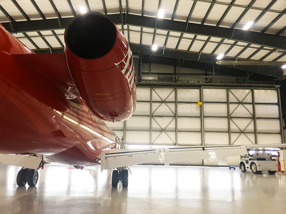 backside of red erj145 inside airplane hangar preparing for takeoff