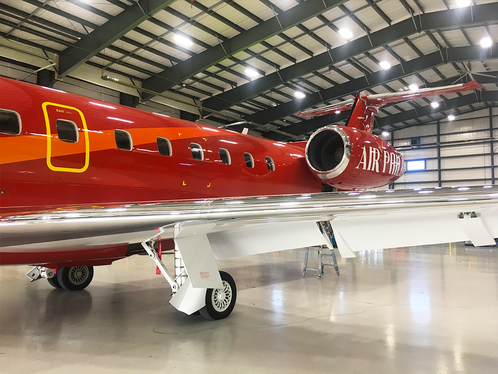 close up of red embraer erj145 exterior paint inside hangar