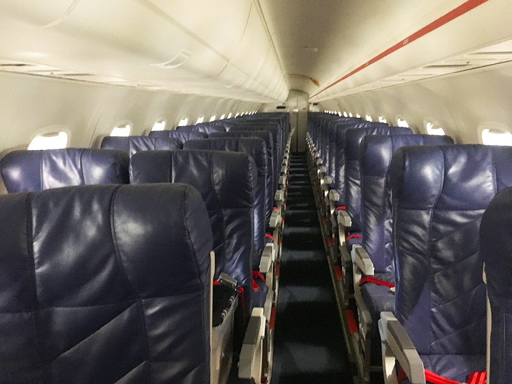 interior of red erj145 airliner with blue leather seats