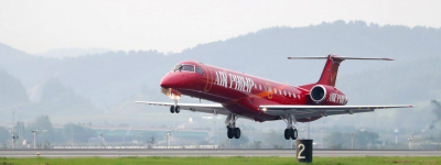 newly painted red embraer erj145 landing on airport runway