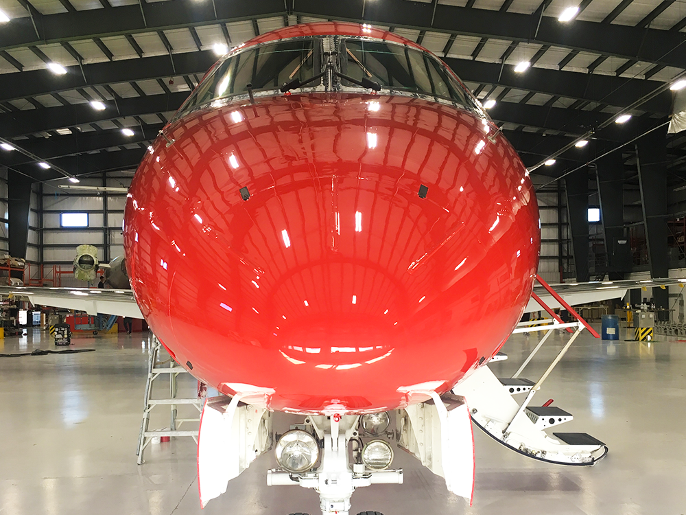 nose of red embraer erj145 inside new united goderich hangar