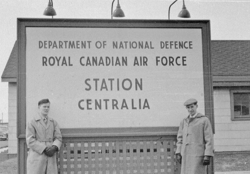 two men outside rcaf station centralia sign