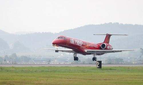 red embraer erj commercial airline landing on runway
